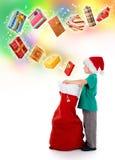 Saco de Santa da abertura do rapaz pequeno com presentes fotos de stock royalty free