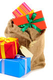 Saco de Santa ou saco da meia completamente com a pilha dos presentes do Natal isolados no fundo branco Foto de Stock Royalty Free