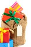 Saco de Santa ou saco do correio completamente com a pilha dos presentes do Natal isolados no fundo branco Fotografia de Stock Royalty Free