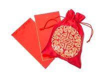Saco de seda vermelho do dinheiro com os envelopes vermelhos lustrosos Fotos de Stock