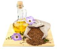 Saco de semillas de lino y de botella de cristal de petróleo Fotografía de archivo libre de regalías