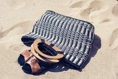 Saco de vime da praia da palha do verão do vintage e sandálias de couro no litoral de Catania, Sicília, Itália foto de stock royalty free