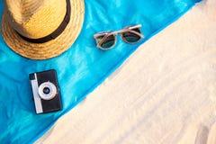 Saco de vime da praia da palha do verão do vintage, vidros de sol, envoltório na areia, fundo tropical do roupa de banho do encob fotos de stock