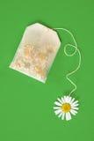 Saco do chá de camomila sobre o fundo verde Imagens de Stock