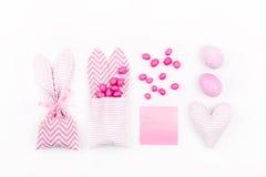 Saco do deleite do coelho com doces cor-de-rosa, o cartão vazio, os ovos e o coração Imagens de Stock Royalty Free