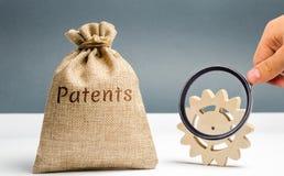 Saco do dinheiro com as patentes da palavra e uma engrenagem de madeira Registro das patentes e da conformidade dos direitos rese foto de stock royalty free