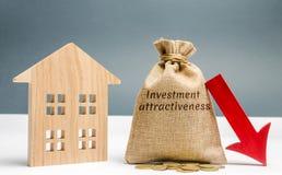 Saco do dinheiro com a atração do investimento da palavra e para baixo uma seta com uma casa Conceito da atração e do investiment imagem de stock