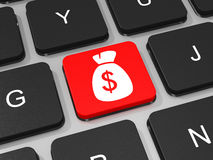 Saco do dinheiro com chave do sinal de dólar no teclado do laptop Fotografia de Stock Royalty Free