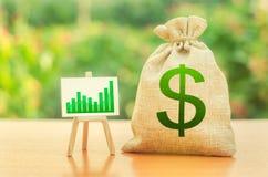 Saco do dinheiro com símbolo do dólar e um suporte com uma carta verde da tendência do crescimento Aumente lucros e riqueza cresc fotografia de stock