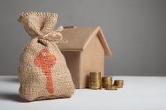 Saco do dinheiro com sinal chave no fundo de moedas de ouro e figuras de crafting a casa ?oncept da compra e do aluguer real fotografia de stock