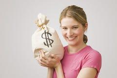 Saco do dinheiro da terra arrendada da mulher Imagem de Stock