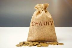 Saco do dinheiro e da caridade da palavra O conceito de acumular o dinheiro para doações saving Ajuda médica social dos voluntári imagens de stock royalty free