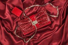 Saco do perfume de couro e vermelho envernizado que encontra-se na seda vermelha Bolsa para mulheres e garrafa do perfume, vista  imagem de stock royalty free