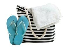 Saco listrado da praia com a toalha de banho branca e batidas de borracha azuis foto de stock