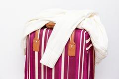 Saco listrado vermelho e branco da bagagem com uma camiseta feita malha nela, fundo branco, conceito mínimo do curso foto de stock