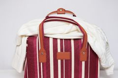 Saco listrado vermelho e branco da bagagem com uma camiseta feita malha nela, fundo branco, conceito mínimo do curso fotografia de stock