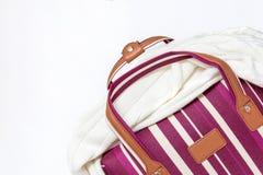 Saco listrado vermelho e branco da bagagem com uma camiseta feita malha nela, fundo branco, conceito mínimo do curso com espaço fotos de stock