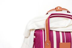 Saco listrado vermelho e branco da bagagem com uma camiseta feita malha nela, fundo branco, conceito mínimo do curso com espaço fotos de stock royalty free