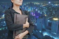 Saco novo da terra arrendada da mulher de neg?cio da exposi??o dobro com paisagem da cidade na noite imagem de stock