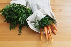 Sacos amig?veis do eco reus?vel com as cenouras dos legumes frescos, r?cula, na tabela de madeira pl?stico da proibi??o Compras n foto de stock