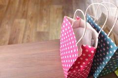 Sacos coloridos com roupa no elev de madeira do fundo do parquet da tabela Imagens de Stock Royalty Free