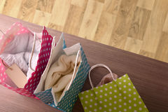 Sacos coloridos com roupa no fundo de madeira da tabela e do parquet Foto de Stock