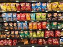 Sacos da microplaqueta de batata na exposição em um supermercado fotografia de stock royalty free