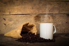 Sacos da xícara de café de feijões de café no assoalho de madeira velho Fotos de Stock Royalty Free