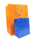 Sacos de compra azuis e alaranjados isolados sobre o branco Foto de Stock