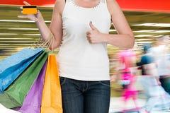 Sacos de compra da terra arrendada da mulher e cartão de crédito Fotografia de Stock