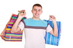 Sacos de compra de sorriso da terra arrendada do homem Imagem de Stock Royalty Free