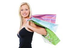 Sacos de compra louros de sorriso da terra arrendada da mulher da beleza Fotos de Stock Royalty Free