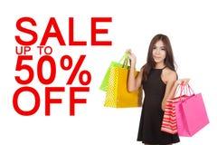 Sacos de compras asiáticos bonitos da posse da mulher com sinal da venda 50% Foto de Stock