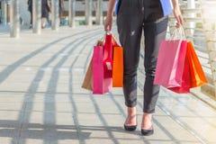 Sacos de compras levando da jovem mulher ao andar ao longo da rua fotos de stock