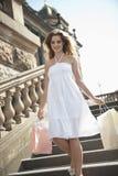Sacos de compras levando da jovem mulher feliz que andam na escadaria fotografia de stock