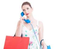 Sacos de compras levando da senhora que têm uma chamada de apoio Imagem de Stock Royalty Free