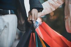 Sacos de compras nas mãos masculinas e fêmeas Passagem dos sacos ou dos presentes, fim acima foto de stock royalty free