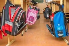 Sacos de escola que penduram em ganchos em ambos os lados do corredor entre as mesas na sala de aula Foto de Stock