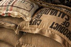 Sacos de la arpillera con los granos de café imagen de archivo