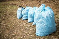 Sacos de lixo azuis na terra Foto de Stock Royalty Free