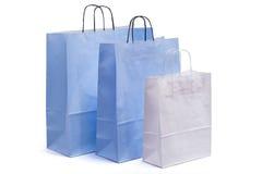 Sacos de papel azuis e brancos com os punhos para comprar Fotografia de Stock Royalty Free