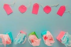 Sacos de papel coloridos do presente e etiquetas cor-de-rosa no fundo azul com c Imagem de Stock Royalty Free