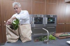 Sacos de papel de Unpacking Groceries From do cozinheiro chefe na cozinha Fotos de Stock