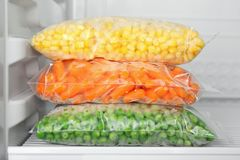 Sacos de plástico com os vegetais congelados no refrigerador fotografia de stock