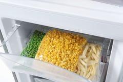 Sacos de plástico com os vegetais congelados no refrigerador fotos de stock royalty free