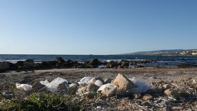 Sacos de pl?stico e lixo do papel na praia suja arenosa Ondas do mar que batem a praia no fundo Movimento lento filme