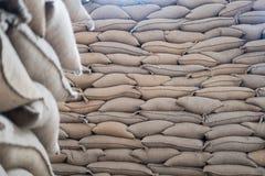 sacos del cáñamo que contienen el grano de café en almacén sacos apilados adentro Foto de archivo