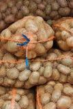 Sacos netos con las patatas en la tienda de alimentación Foto de archivo