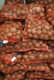 Sacos netos con las patatas en la tienda de alimentación Imagen de archivo libre de regalías