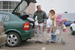 Sacos põr família da loja no carro fotos de stock